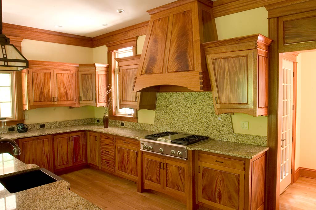 The custom range hood features crotch mahogany and a remote fan. The handcut dovetails on the hood also appear in all the drawers & the frieze board of the cabinets.