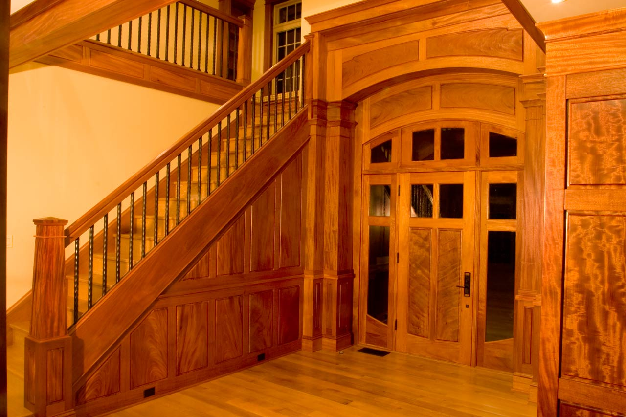 The foyer has a graceful elliptical arch transom which is echoed by double arching panels and double columns. The stairs and floor are quartersawn white oak.