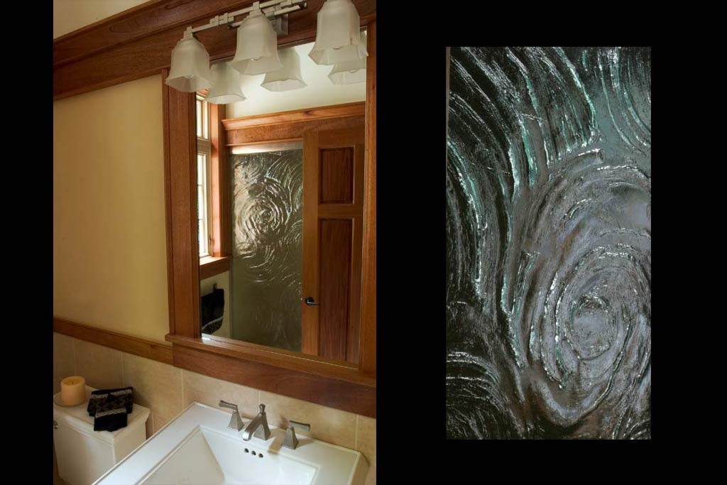 The powder room has a craftsman theme bringing the crown off the ceiling to the top of the door and shower. The cast art glass serves as a screen for the shower.