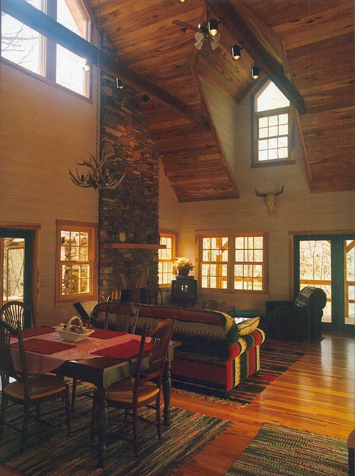 The great room floor and ceiling are hickory, the chimney is local fieldstone and the walls are a pickled pine tongue and groove paneling.