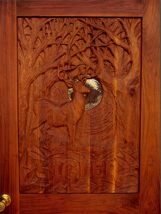 "This door was a collaboration with sculptor Bill Hopen of Sutton. Hopen designed the scene and carved the panel with Michael Corlis. The moon is a piece of 1"" hand blown Blenko Glass."