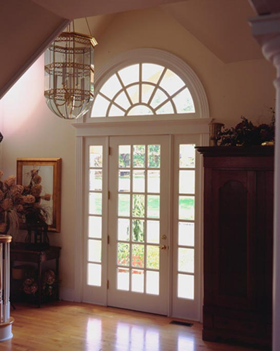 The custom made entry door features beveled glass and graces the cathedral entry foyer.
