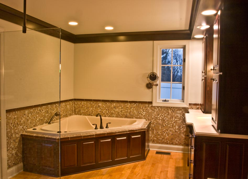The master bathroom is executed in custom made mahogany cabinets, paneling, maple floor and glass tile.